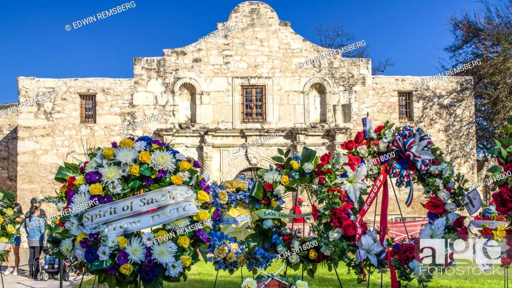 Stock Photo: Wreaths of flowers place out in front of the iconic facade of the Alamo Mission, San Antonio, TX.