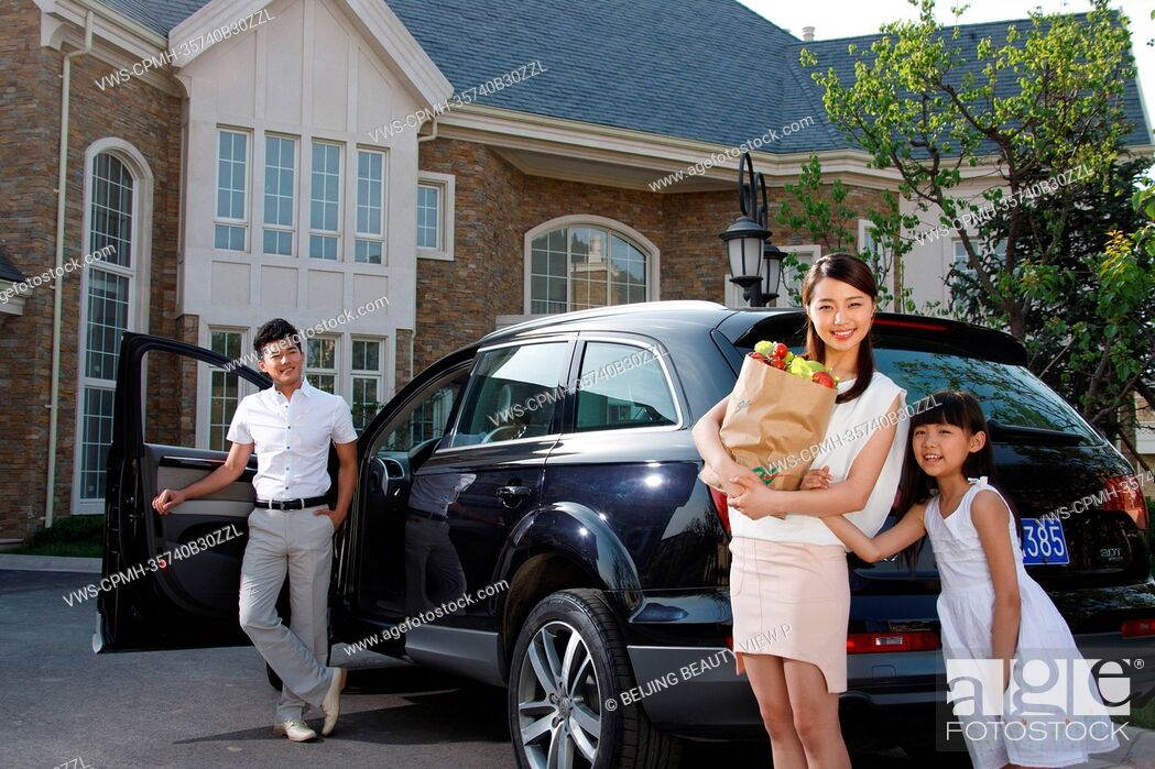 Stock Photo: Oriental family standing be car holding food.