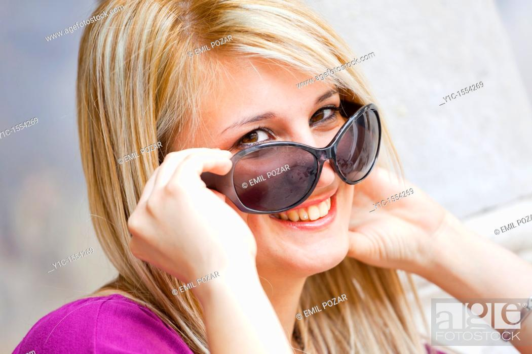Stock Photo: Attractive young woman happy and smiling looking over sunglasses.
