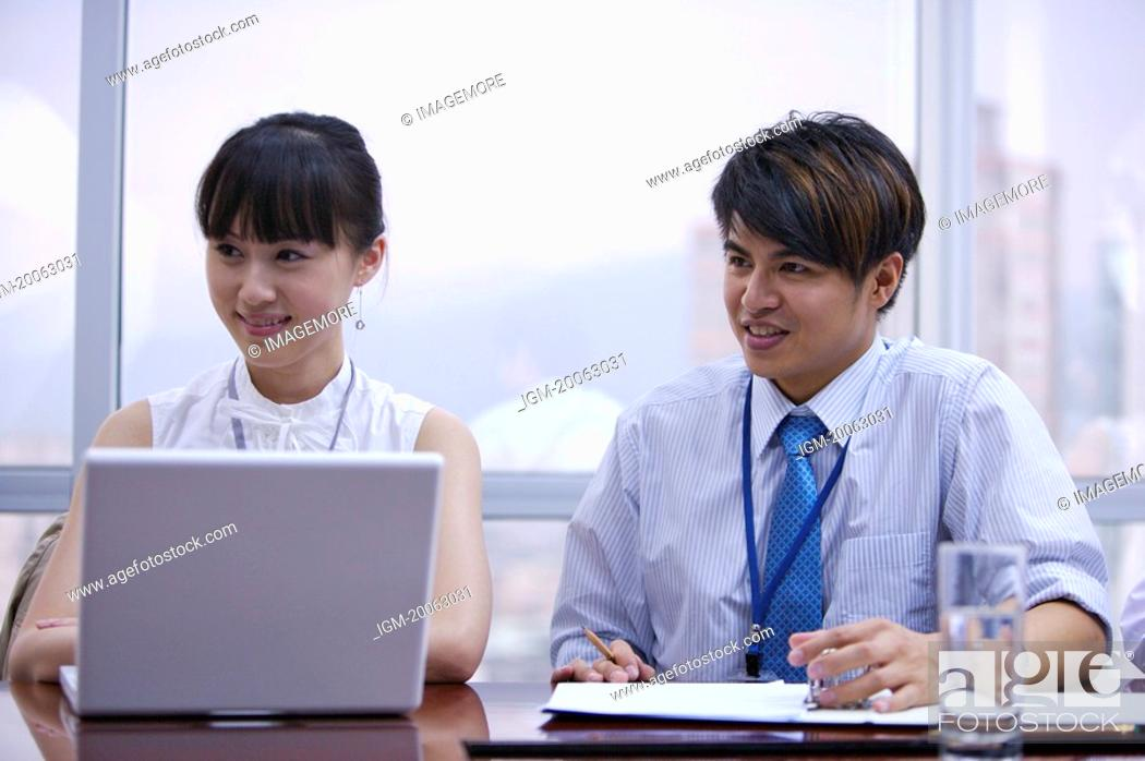 Stock Photo: Young man and woman sitting in office and looking away with smile.