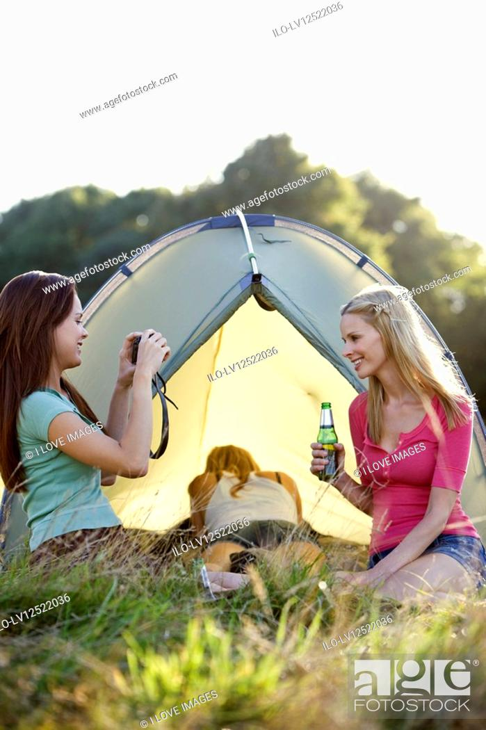 Stock Photo: Three young women camping, one taking a photo.