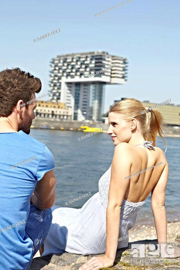 Stock Photo: Germany, Cologne, Young couple sitting on riverbank.