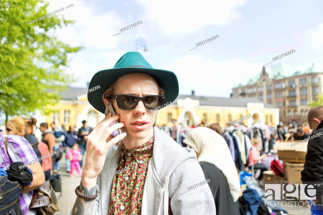 Stock Photo: Man wearing sunglasses talking on phone at flea market.