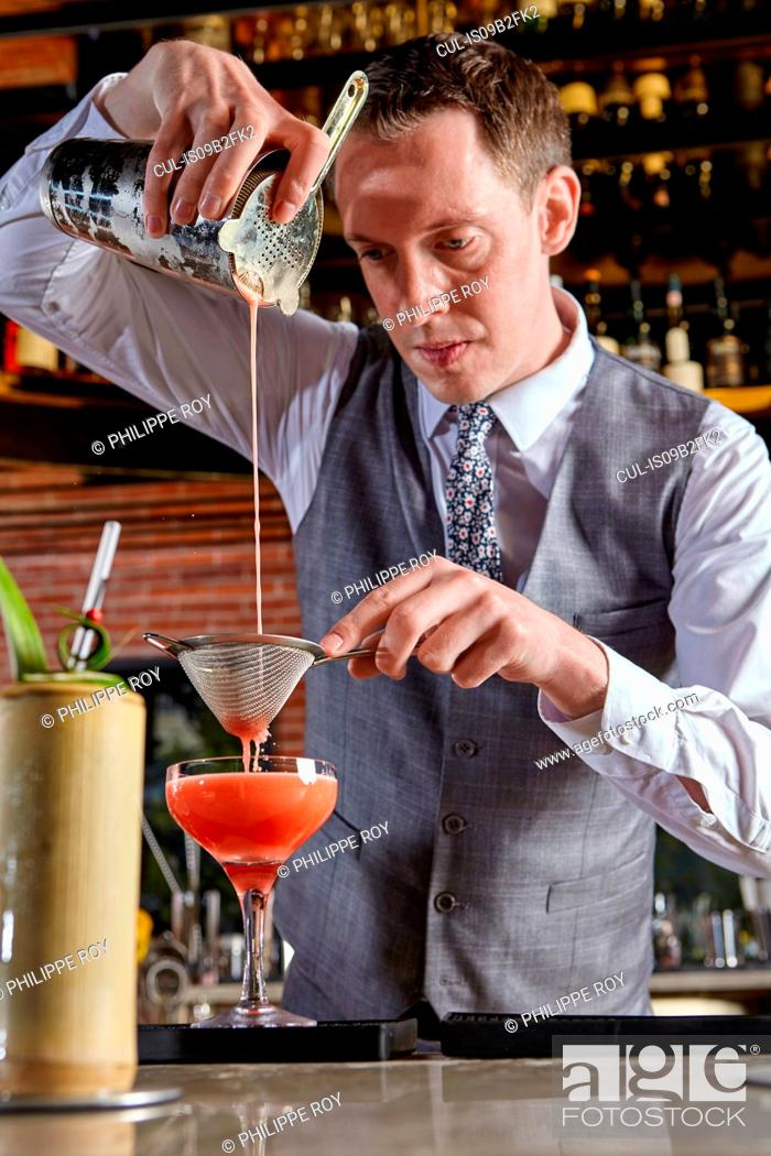 Stock Photo: Bartender pouring cocktail.