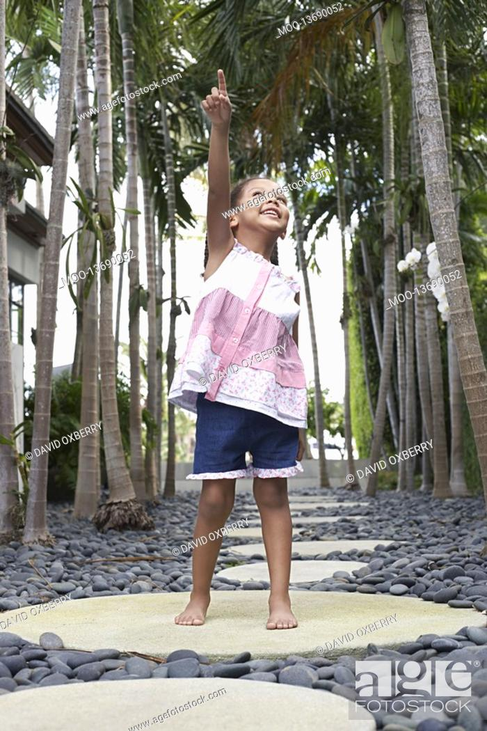 Stock Photo: Girl 5-6 years standing on stepping stone on path pointing up.