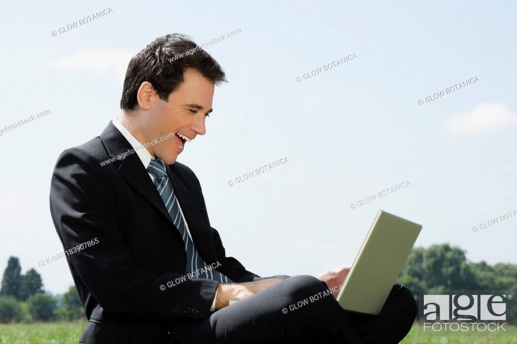 Stock Photo: Businessman using a laptop and laughing.