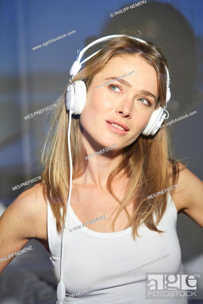 Stock Photo: Portrait of woman behind windowpane listening music with headphones.