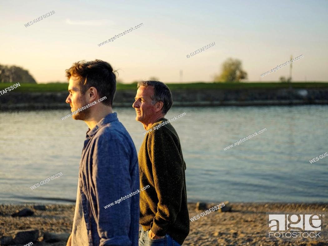 Stock Photo: Father and son looking away while spending leisure time by river at evening.