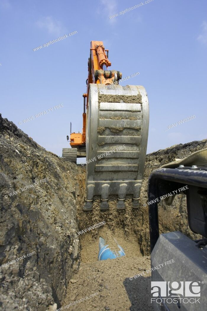 Stock Photo: Excavator filling in section of drainage pipe with dirt, Canada, Ontario, Hamilton Composting Facility.