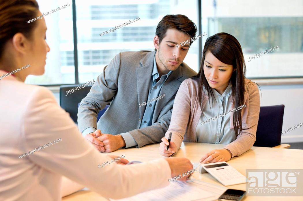 Stock Photo: Couple signing documents with business executive.