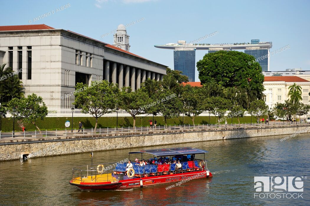 Stock Photo: Motorboat bringing a group of tourists on a ride along Singapore river The large building with columns is the Singapore Parliament while the modern three towers.