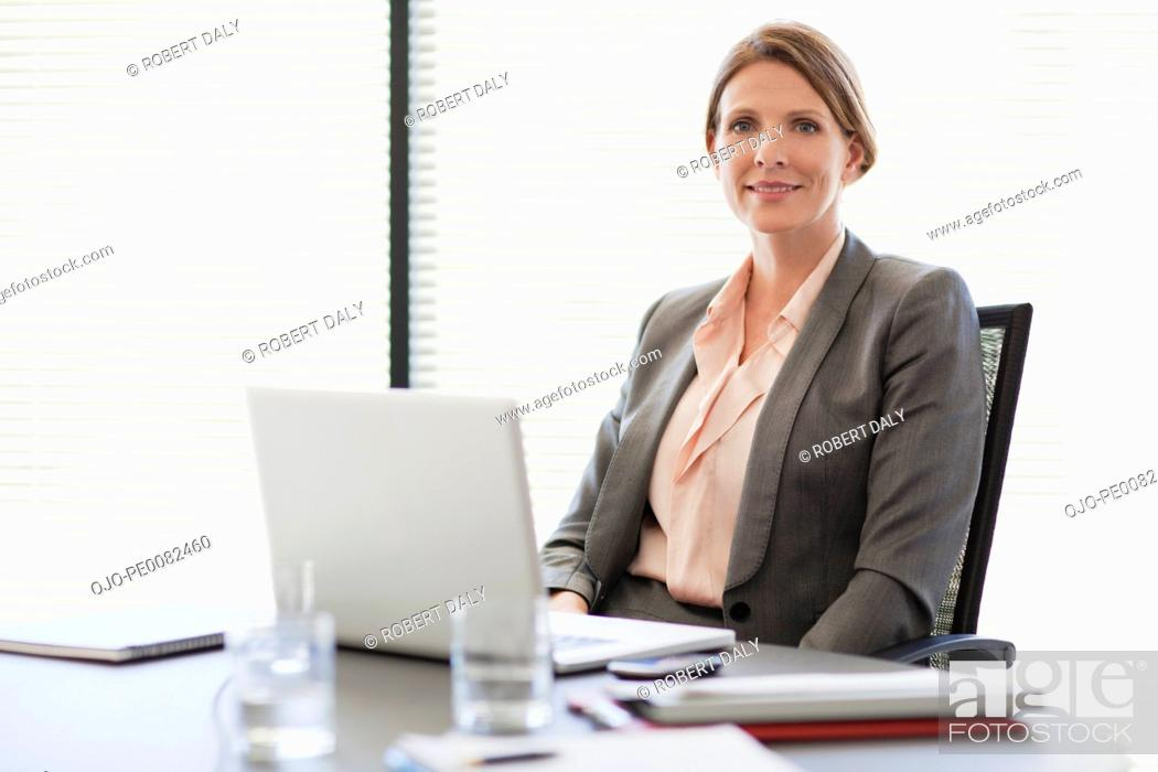 Stock Photo: Portrait of smiling businesswoman with laptop.