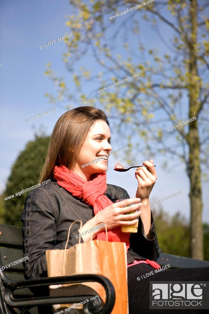 Stock Photo: A young woman sitting on a bench, eating.