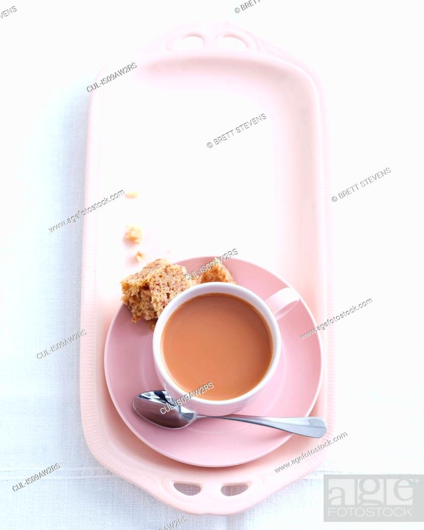 Photo de stock: Overhead view of teacup and saucer on high tea dish with eaten sandwich.