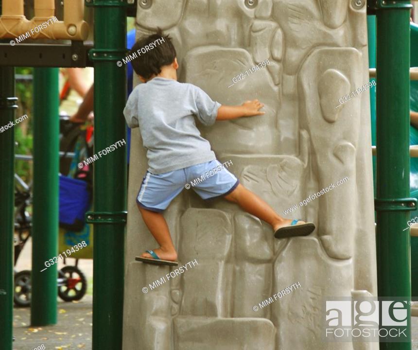 Stock Photo: Boy climbs at playground.