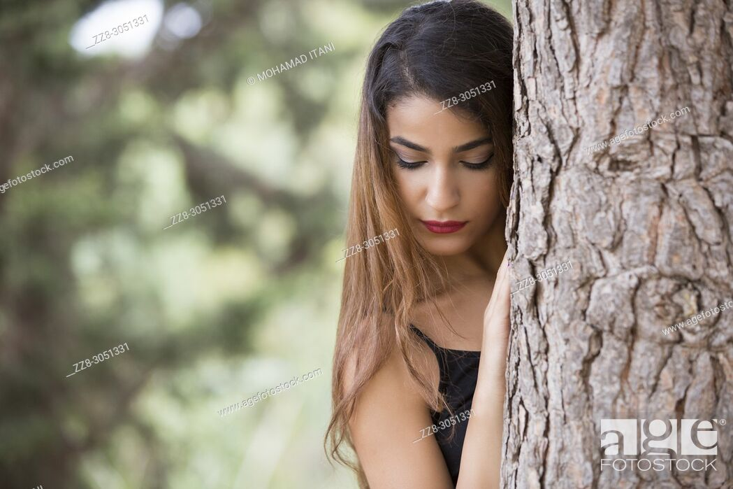 Stock Photo: Sad young woman hiding behind a tree.