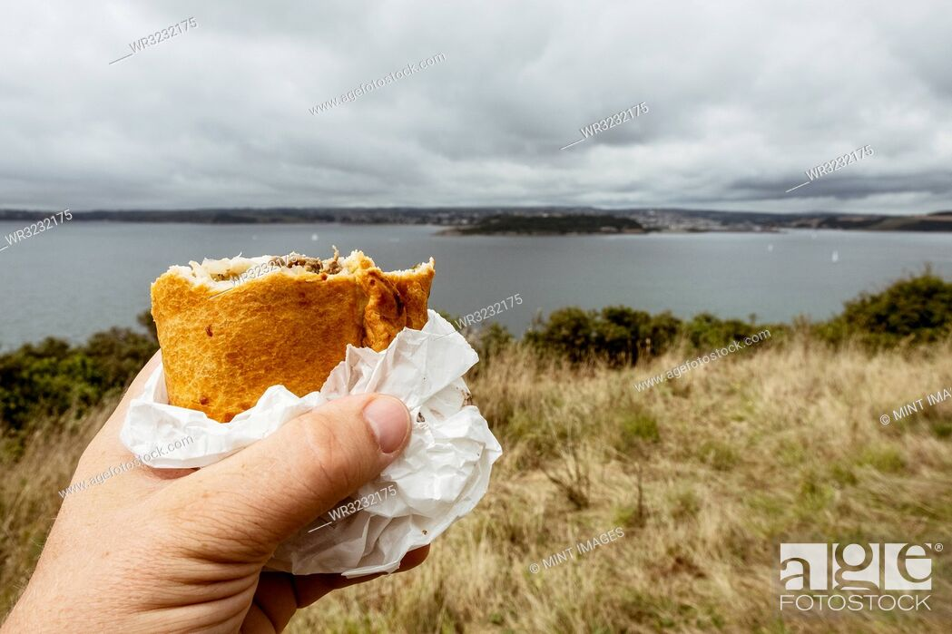 Stock Photo: A hand holding a half eaten Cornish pasty.