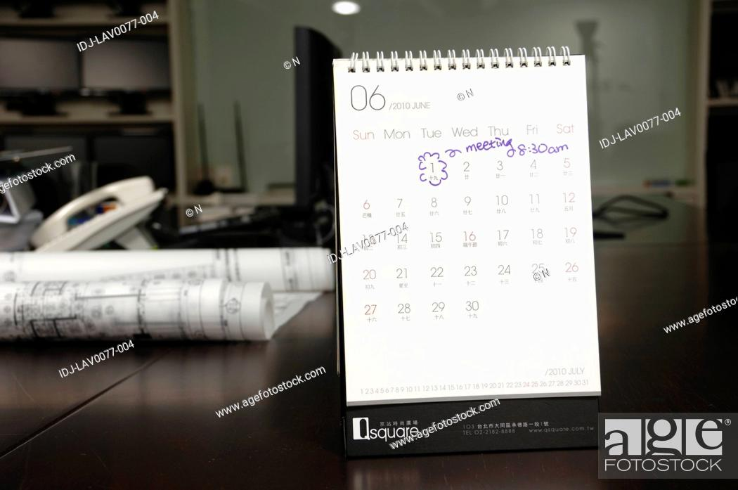 Stock Photo: Marking on a calendar in an office.
