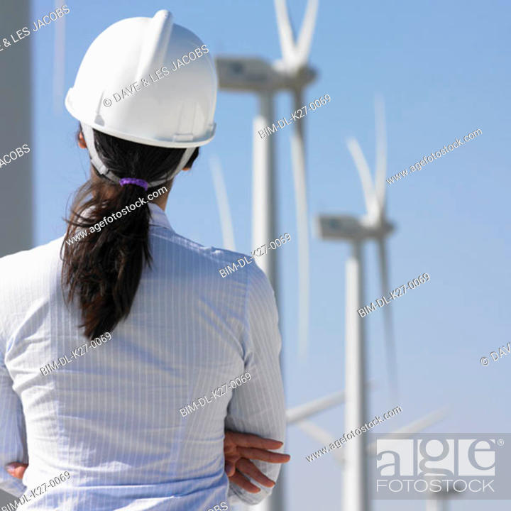 Stock Photo: Female engineer examining wind turbines.
