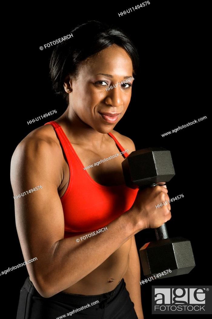 Stock Photo: African American young adult woman holding dumbbell and looking at viewer.