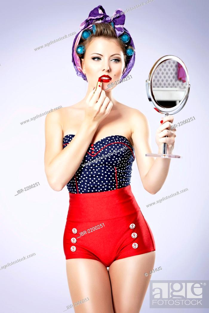 Stock Photo: Young woman wearing hair curlers and hot pants looking in a hand mirror, pin-up.