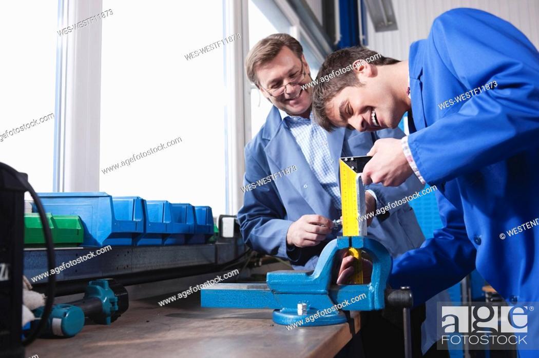 Stock Photo: Germany, Neukirch, Apprentice working on bench vice.