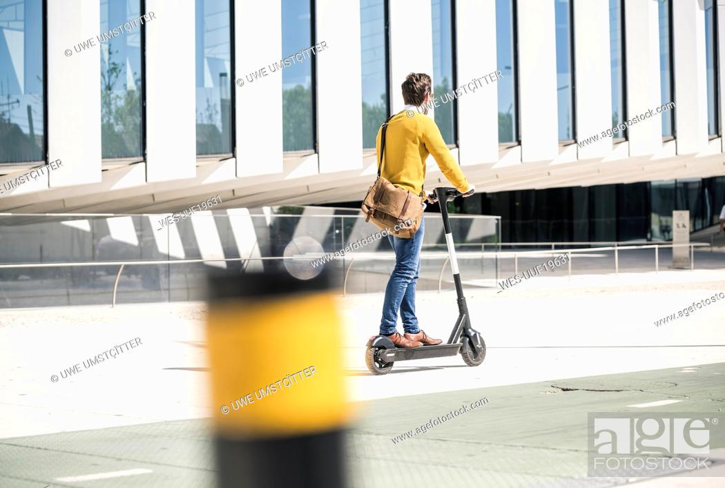Photo de stock: Young man riding e-scooter in the city.