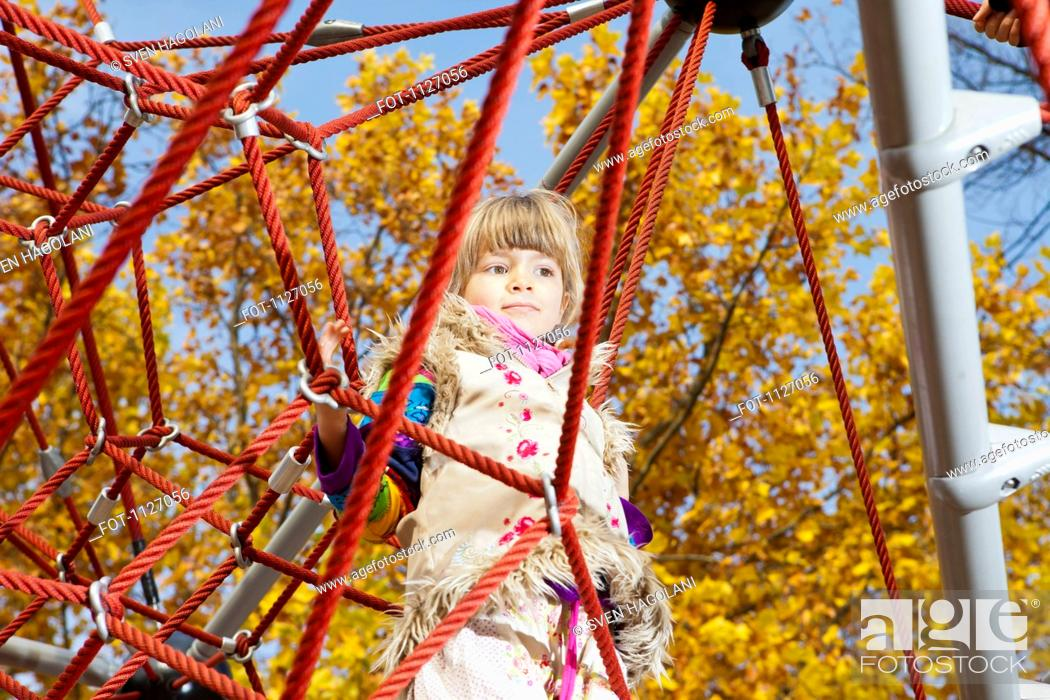 Stock Photo: Girl daydreaming on jungle gym.