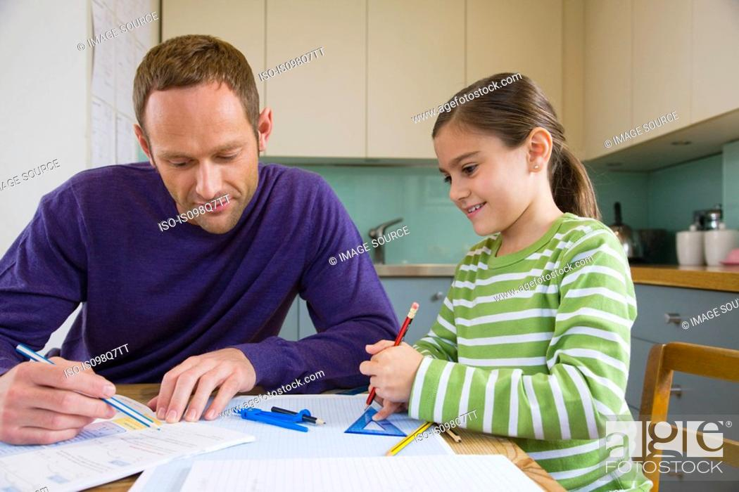 Stock Photo: Father helping his daughter with homework.