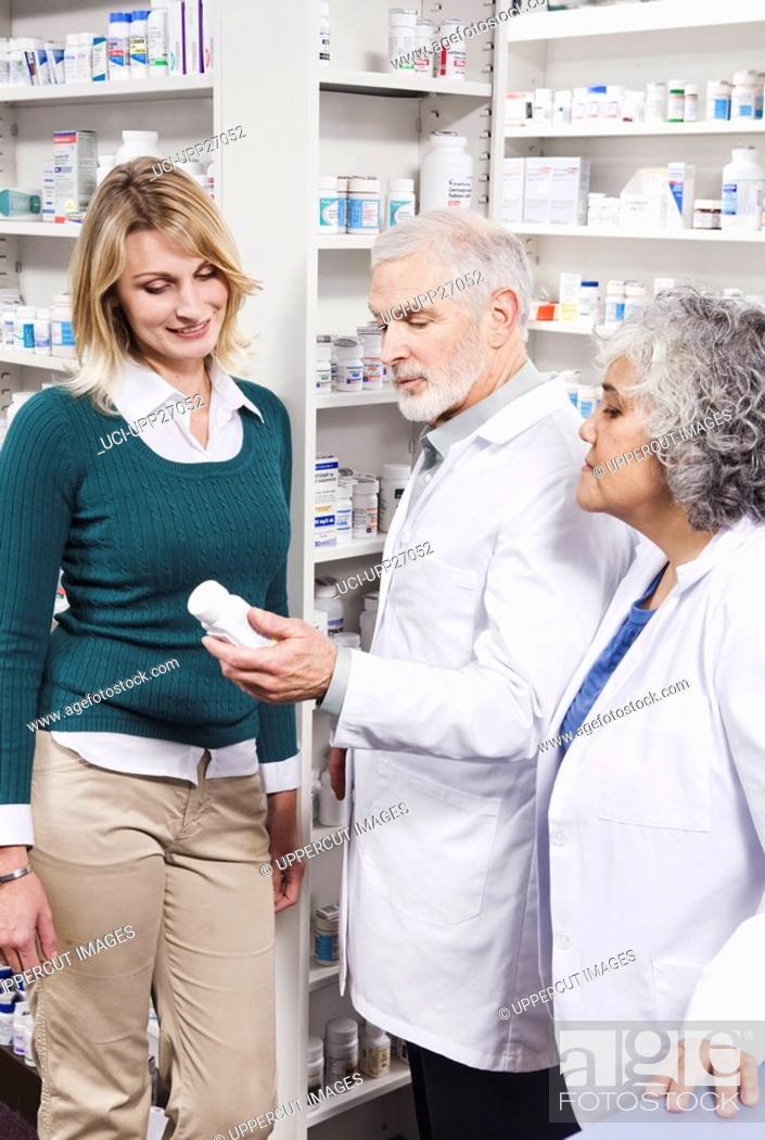 Stock Photo: Pharmacists explaining medication to customer.