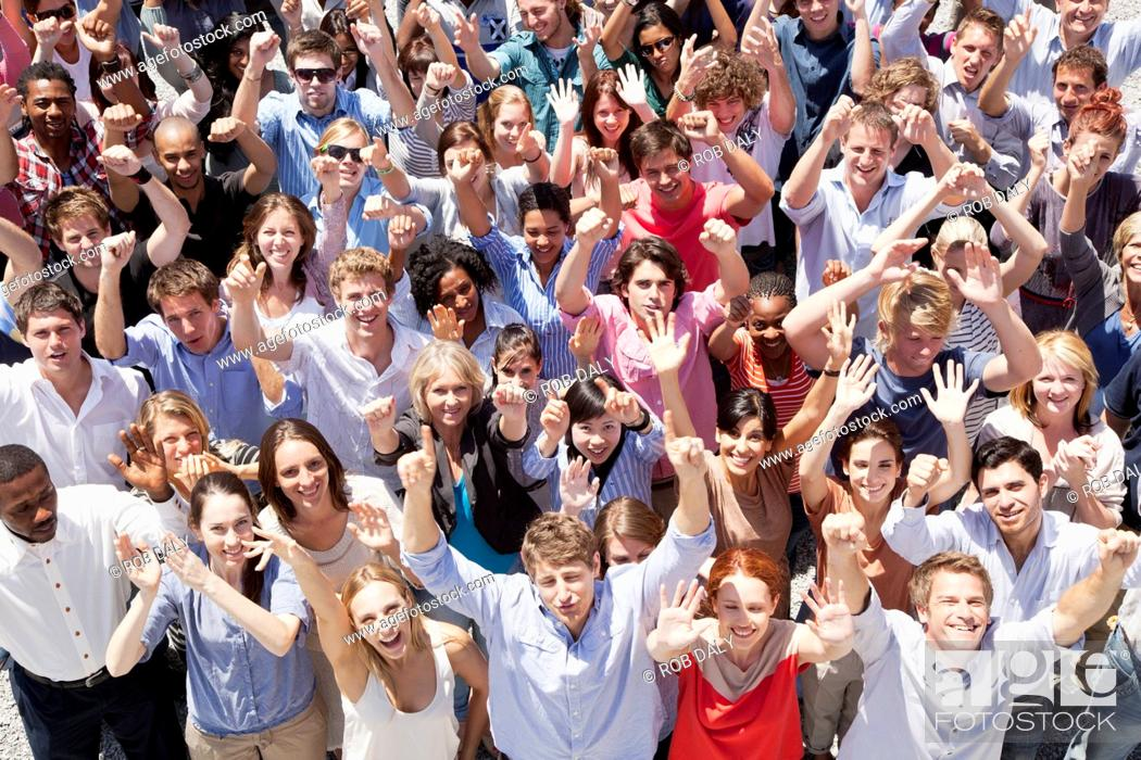 Stock Photo: Portrait of crowd cheering with arms raised.
