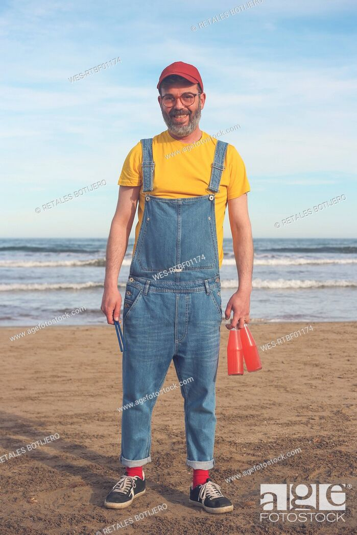 Stock Photo: Portrait of smiling man in dungarees standing on the beach holding bottles of soft drinks.