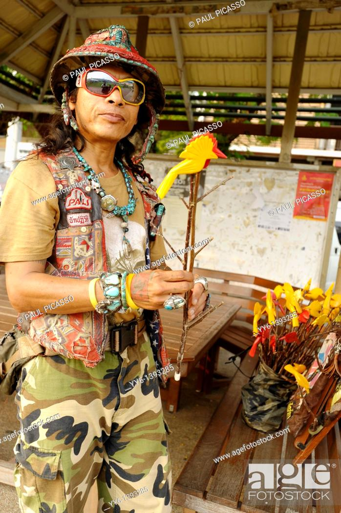 Stock Photo: guy selling red and yellow peace doves made from wood , strange people, street life , bangkok, Thailand.