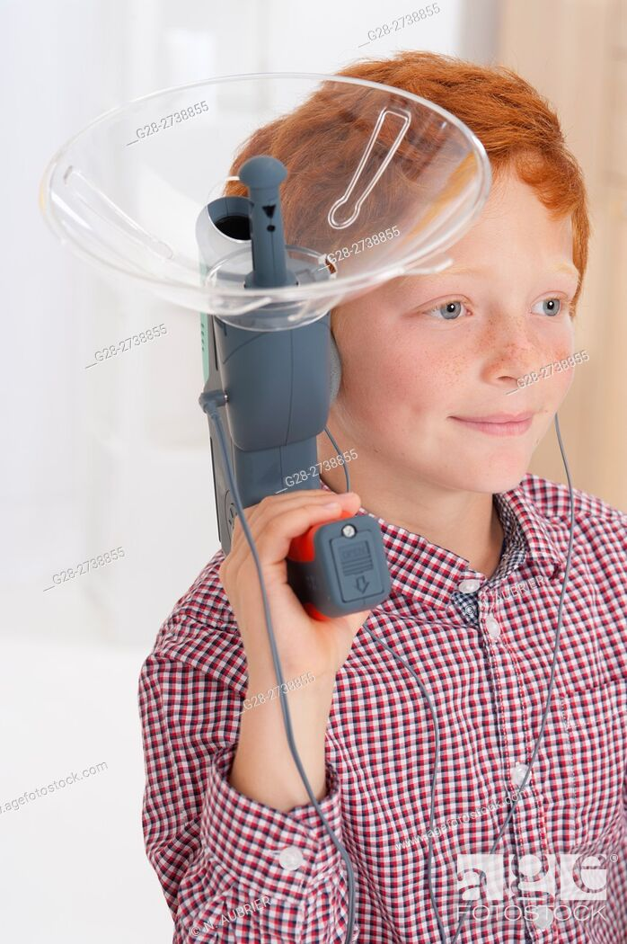 Stock Photo: 6 year old boy using a sound amplifying spy device.