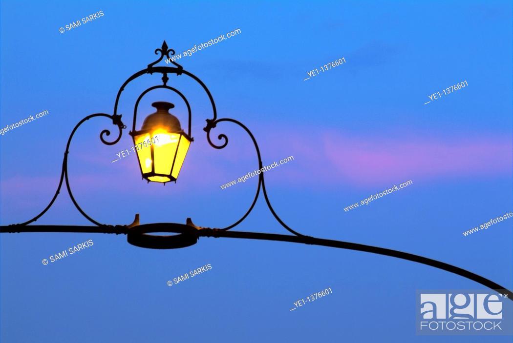 Stock Photo: Wrought iron lamp illuminated at dusk, Carcassonne, France.