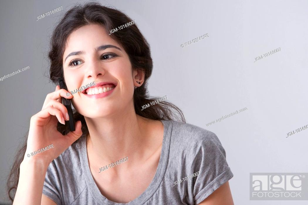 Stock Photo: Young woman talking on the phone happily.