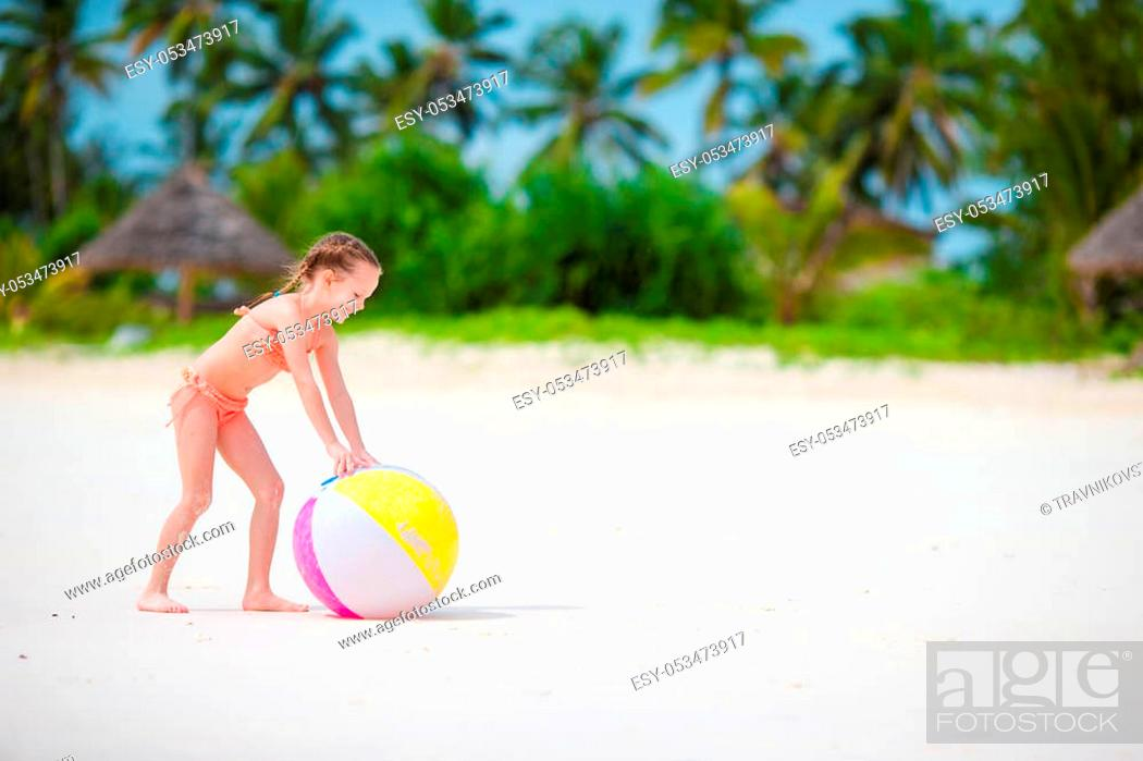 Stock Photo: Cute little girl playing with ball on beach.