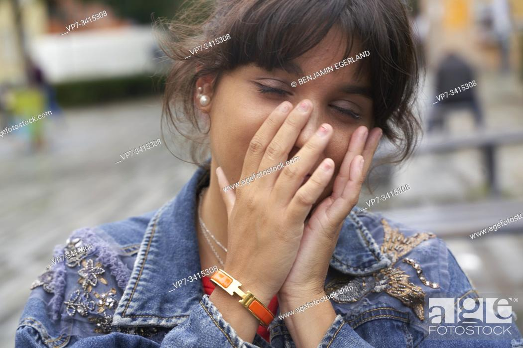 Stock Photo: Close-up portrait of young woman with hands covering her face.