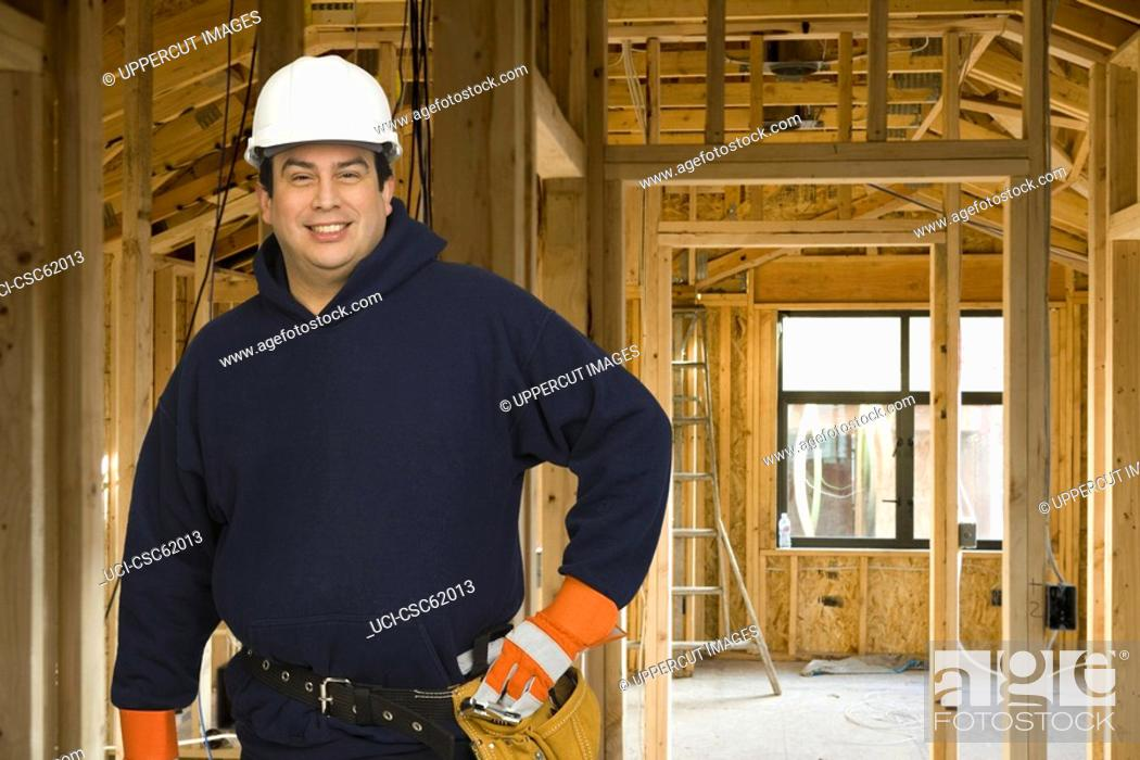 Stock Photo: Male construction worker in front of heavy machinery.