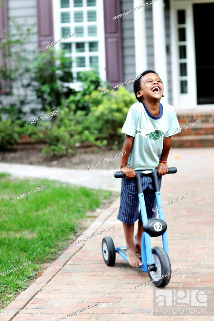 Stock Photo: A carefree boy laughing while riding a push scooter.