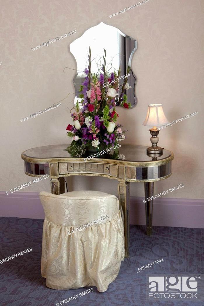 Stock Photo: Mirror Mounted On Wall Over Bouquet And Lit Lamp On Dressing  Table.