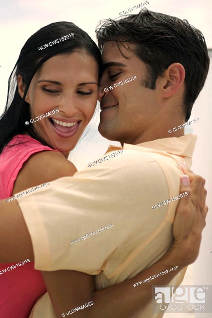 Stock Photo: Side profile of a young woman and a mid adult man embracing each other.
