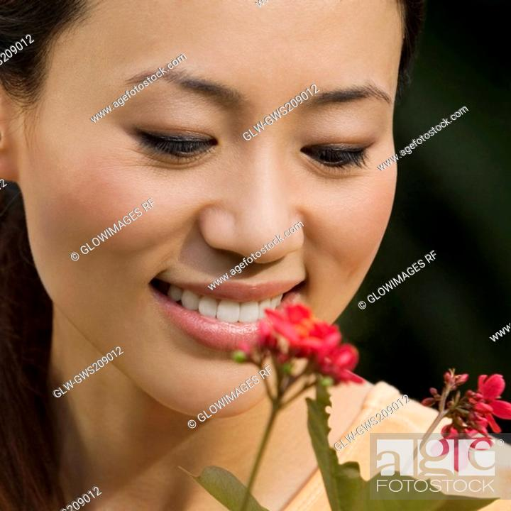Stock Photo: Close-up of a young woman looking at a flower and smiling.