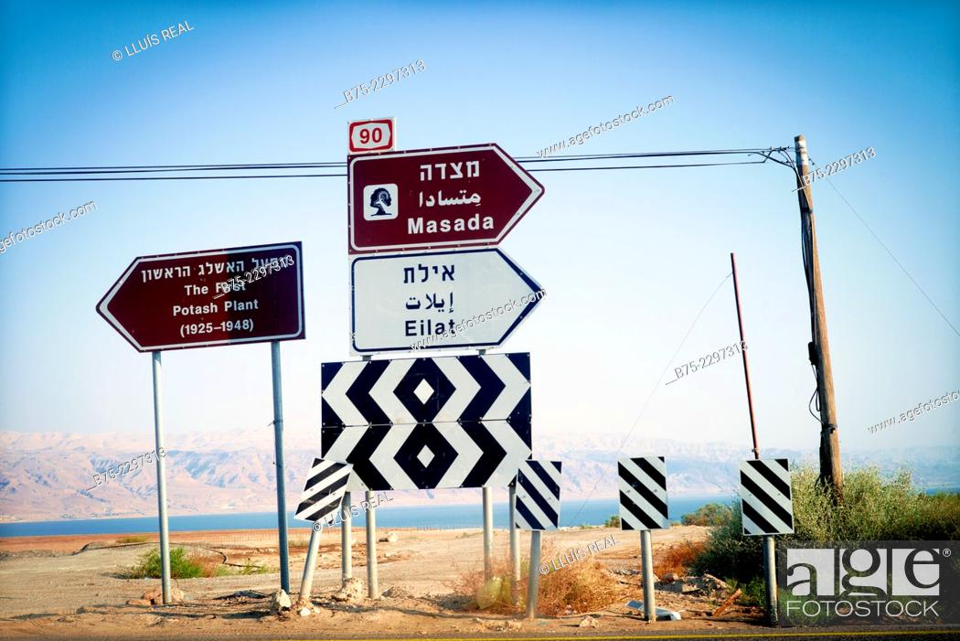 Stock Photo: View of a several road signs indicating different places: Masada, Eilat and the first Potash Plant (1925-1948), with the Death sea on the background, Israel.