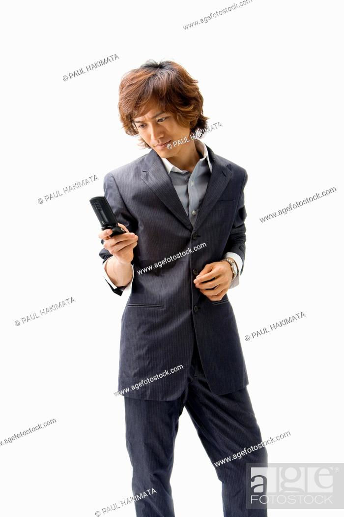 Stock Photo: Young Asian business man with mobile phone texting, isolated.