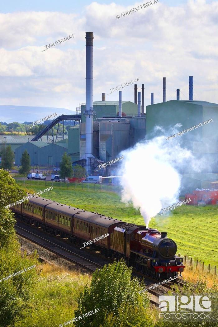 Stock Photo: LMS Jubilee Class 45699 Galatea passing British Gypsum, plaster and plasterboard plant. Kirkby Thore Eden Valley, Cumbria, Settle to Carlisle Railway Line.