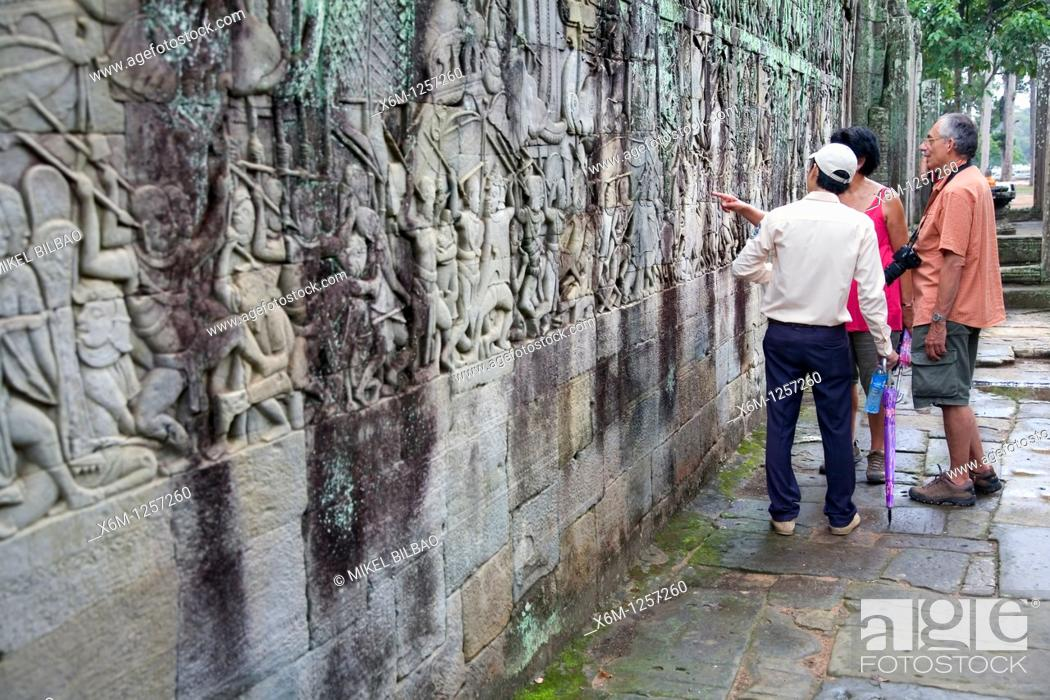 Stock Photo: battle scene bas-relieves and tourists in Angkor Thom temple  Angkor temples, Cambodia, Asia.