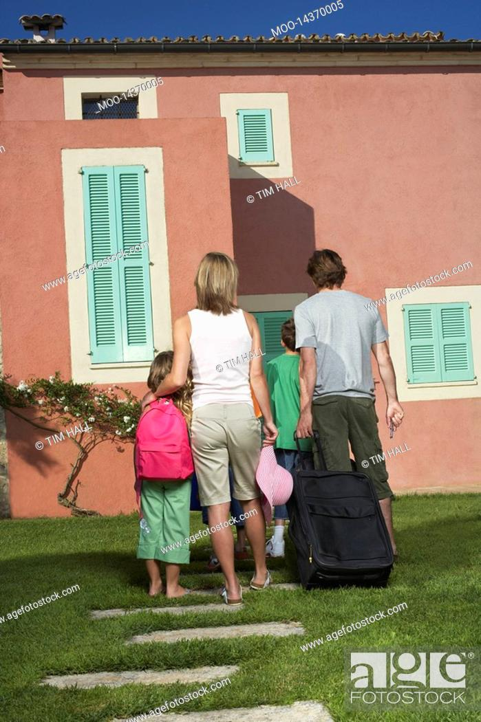 Stock Photo: Family with three children 6-11 entering house with luggage back view.