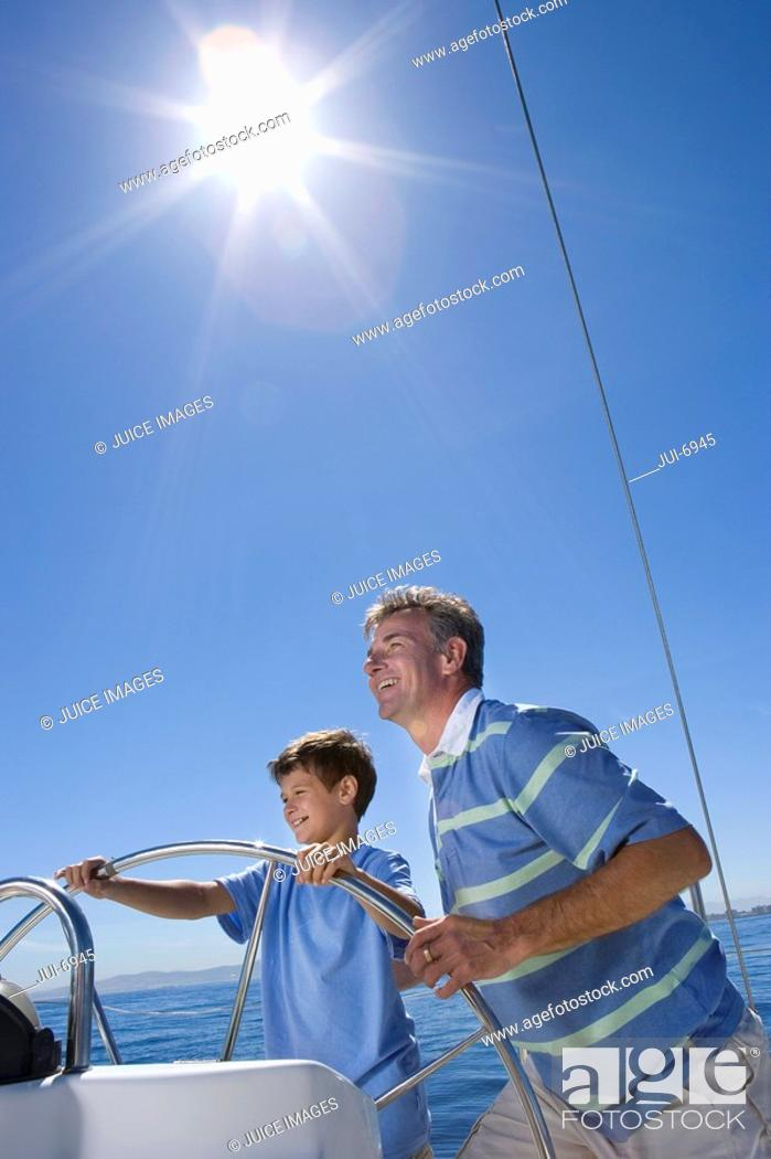 Stock Photo: Father and son 8-10 standing at helm of sailing boat out at sea, steering lens flare, tilt.