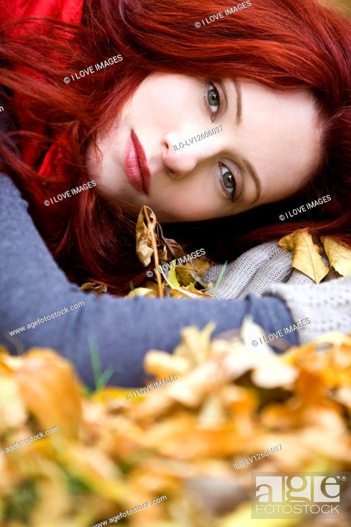 Stock Photo: A portrait of a young woman lying on autumn leaves.